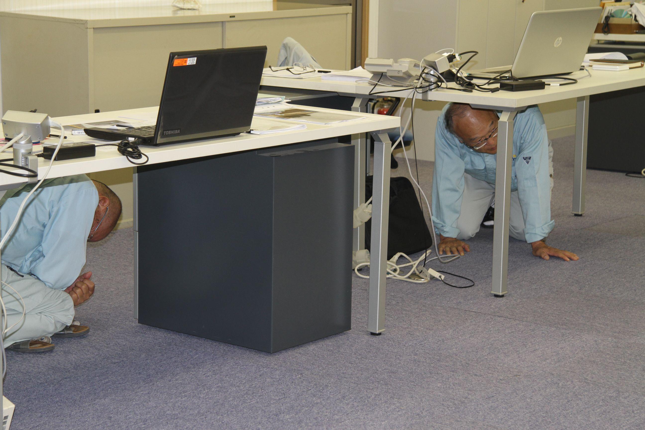 緊急地震速報!揺れが収まるまで、机の下に避難